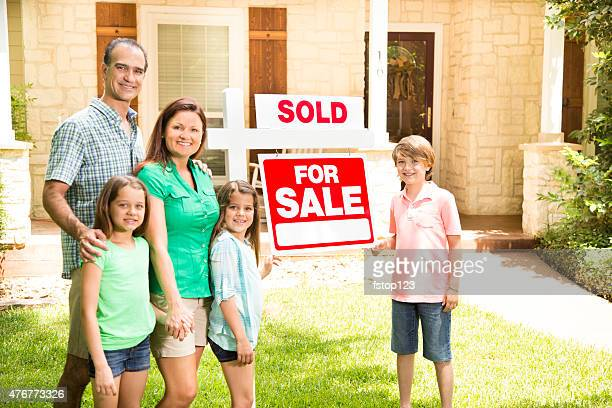 Family with 'house for sale, sold' real estate sign. Summer.