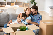 Family with kid embracing on sofa moving in new home