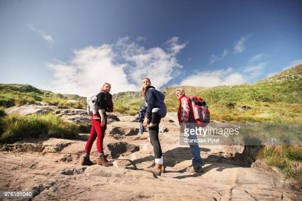 Family with kids in baby carriers trekking in mountains