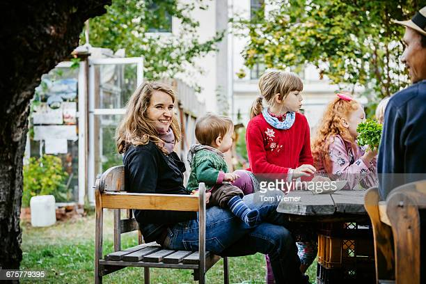 Family with kids sitting in a community garden