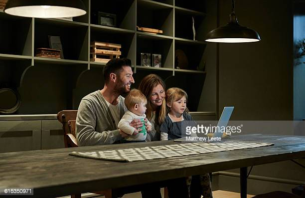 family with laptop - mom sits on sons lap stock pictures, royalty-free photos & images