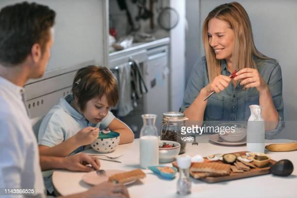 family with little boy with cochlear implant having healthy breakfast - cochlear implant stock pictures, royalty-free photos & images