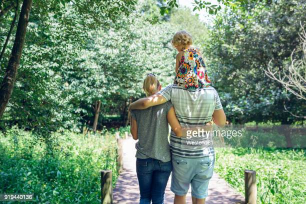 Family with little girl walking on a wooden walkway in the countryside