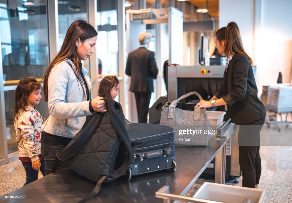 Family with luggage at airport security check : Stock Photo