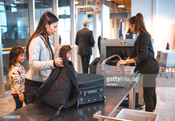 family with luggage at airport security check - security scanner stock pictures, royalty-free photos & images