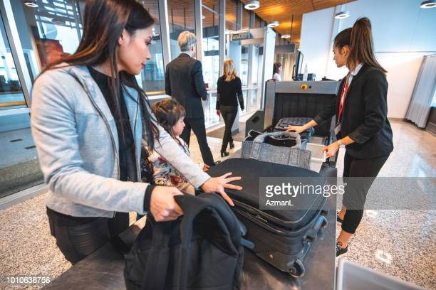 family with luggage at airport security check - security stock pictures, royalty-free photos & images
