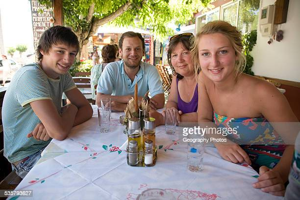 family with mother and three young adult children sitting around a table on holiday in Greece