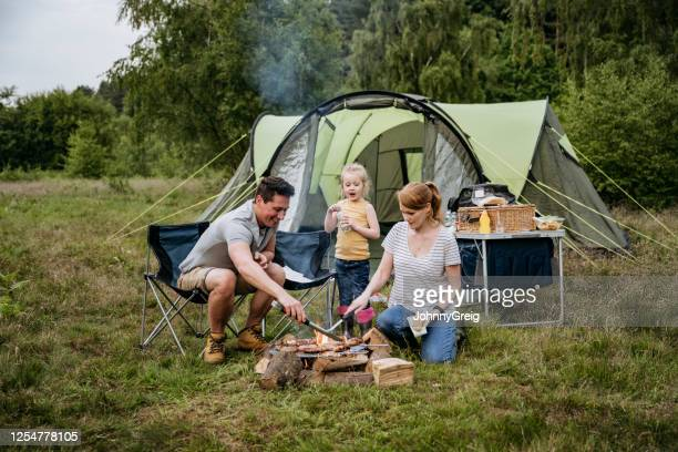 family with one child cooking over open fire on camping trip - tent stock pictures, royalty-free photos & images