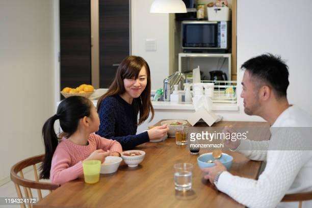 ダイニングルームで食事をする子供が一人いる家族 - ダイニングテーブル ストックフォトと画像