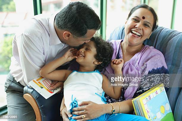 family with one child, father kissing daughter's head, mother smiling at camera - indian girl kissing stock photos and pictures