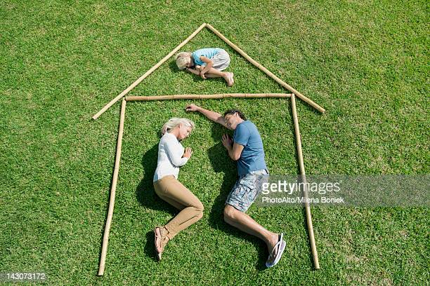 Family with one child lying on grass within outline of house, high angle view