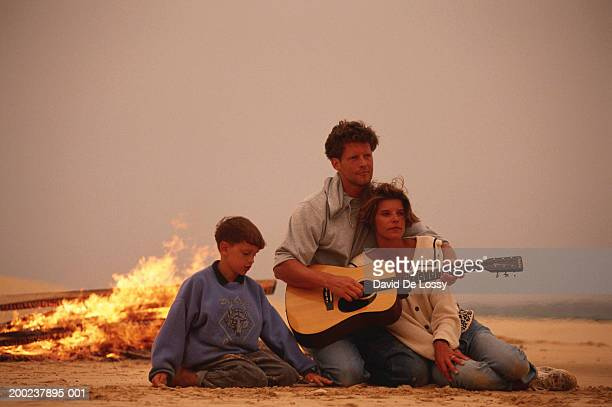 Family with one child sitting by campfire at beach, man playing guitar