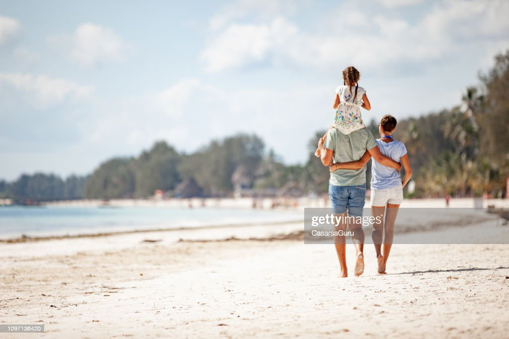 Family WIth One Daughter Walking on Sandy Beach : Foto stock