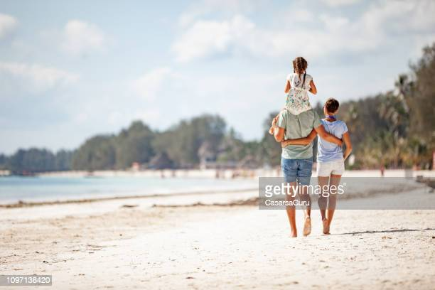 family with one daughter walking on sandy beach - vacanze foto e immagini stock