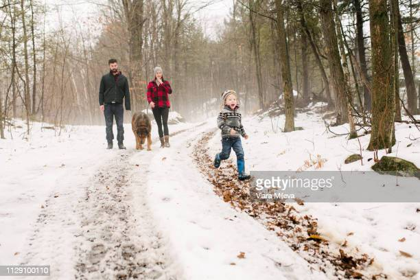 family with pet dog on walk in snow landscape - hundeartige stock-fotos und bilder