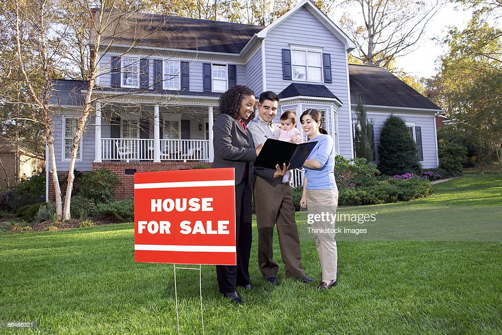 Family with real estate agent outside house : Stock Photo