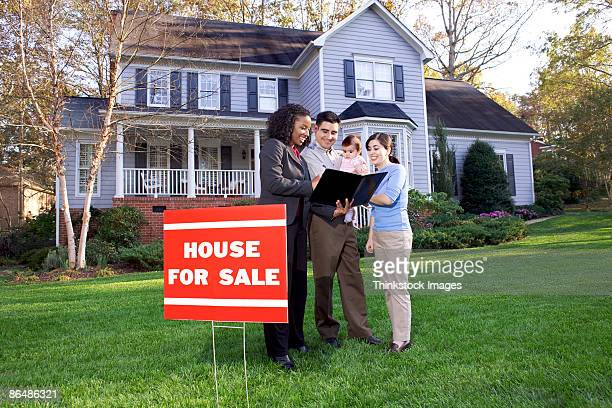 Family with real estate agent outside house