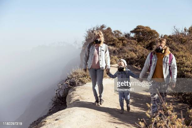 family with respirator masks walking hand in hand along the edge of volcano ijen, java, indonesia - java stock pictures, royalty-free photos & images
