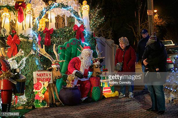Family with santa mannequin older woman smiling, many lights and christmas decorations, Dyker Heights, Brooklyn, New York City