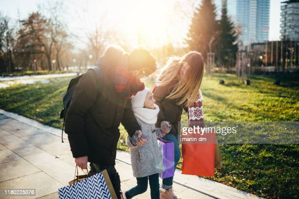 family with shopping bags after black friday day - black friday stock photos and pictures