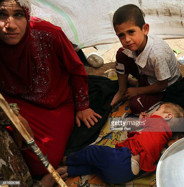 A family with sick children takes shelter under a sheet as thousands of Iraqis who have fled recent fighting in the cities of Mosul and Tal Afar try...