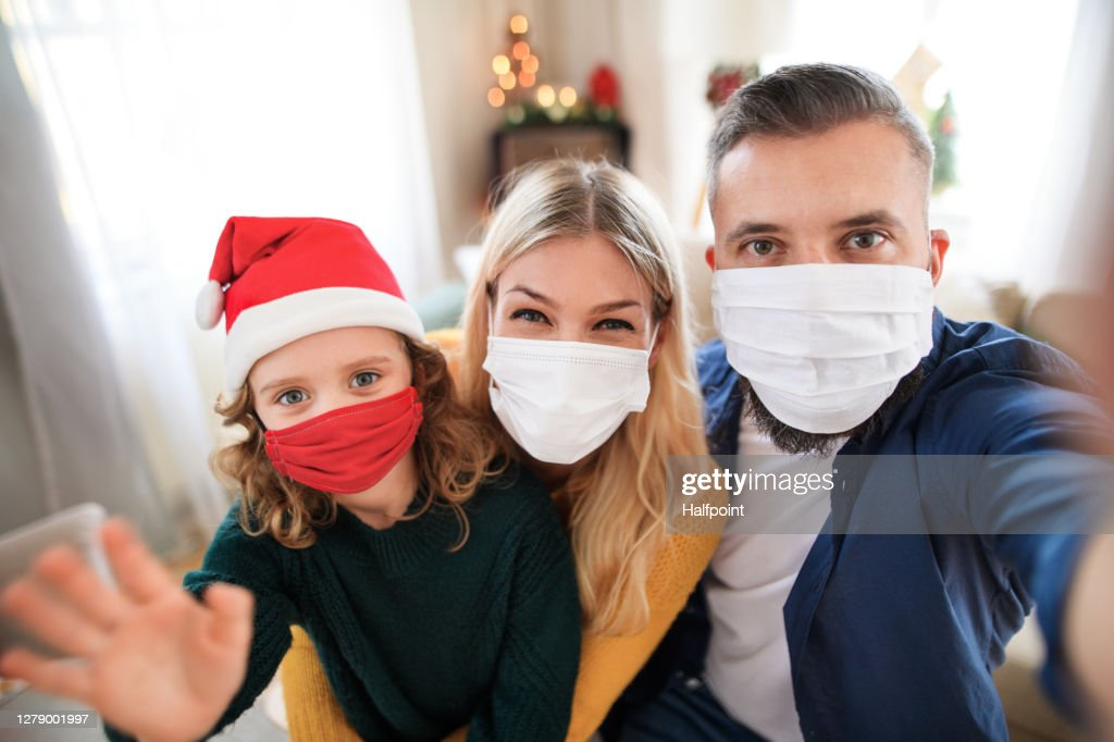 Family with small daughter indoors at home at Christmas, taking selfie with face masks. : Stock Photo