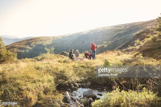 Family with small kids taking break during trekking in mountains