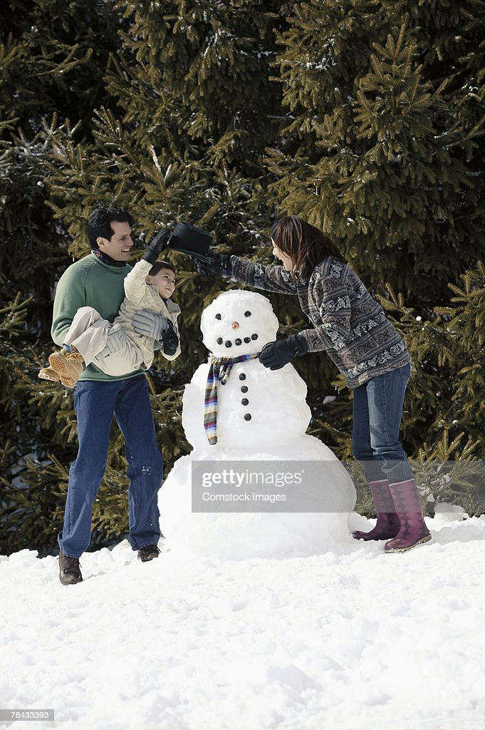 Family with snowman : Stockfoto