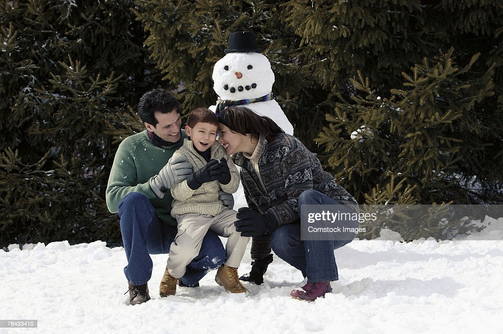 Family with snowman : Stock Photo