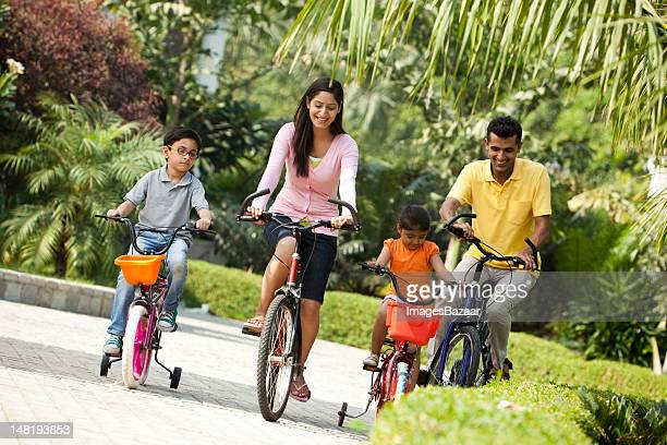Family with son and daughter (6-7) riding bikes in park