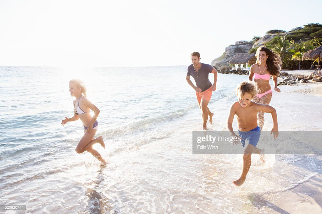Family with son (8-9) and daughter (10-11) running on beach : Stock Photo