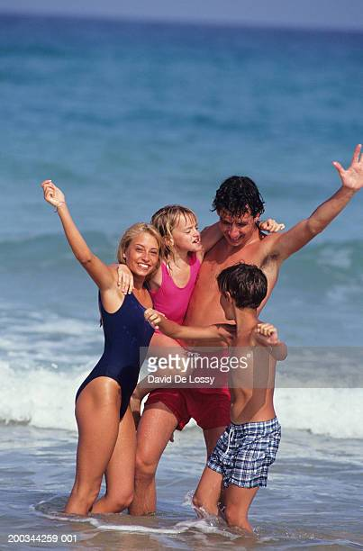 Family with son (10-11) and daughter (4-5) standing in sea