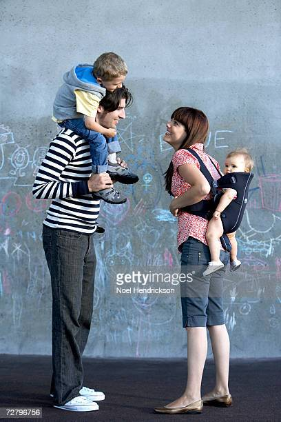 family with son (3-4 years) on fathers shoulders and baby (6-9 months) on mothers back - 30 34 years fotografías e imágenes de stock