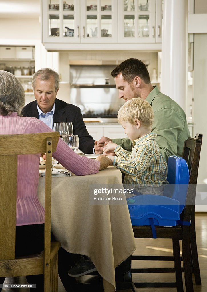 Family with son (2-3 years) saying Grace at Dinner Table : Foto stock