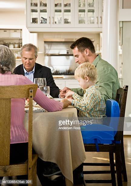 family with son (2-3 years) saying grace at dinner table - 55 59 years stock pictures, royalty-free photos & images