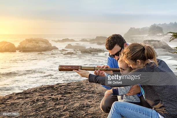 Family with spyglass looking toward ocean