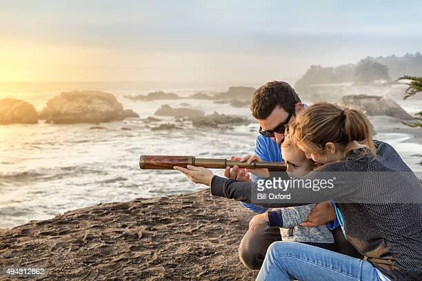 Familia con spyglass mirando hacia al mar