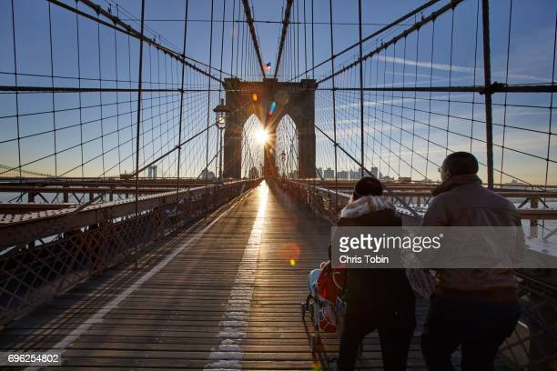Family with stroller walking along Brooklyn Bridge looking into the sun