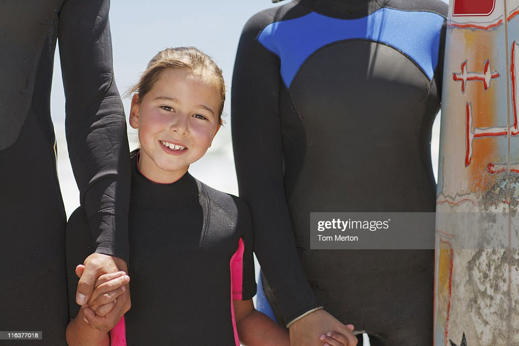 Family with surfboard holding hands in wetsuits : Stock Photo