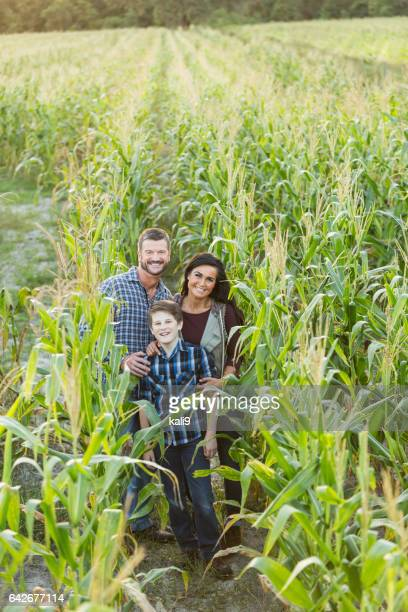 Family with teenage son on a farm in corn field