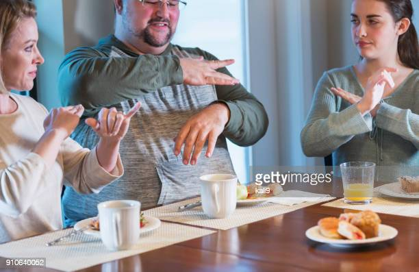 Family with teenager at breakfast, using sign language