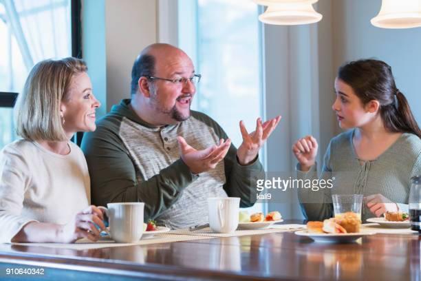 Familia con hijo adolescente en el desayuno, uso de lenguaje de señas