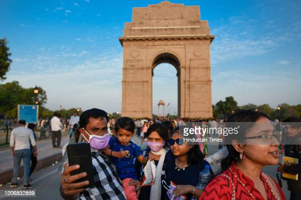 A family with their faces covered with protective face masks take a selfie at India Gate as India suspended all tourist visas until April 15 in the...