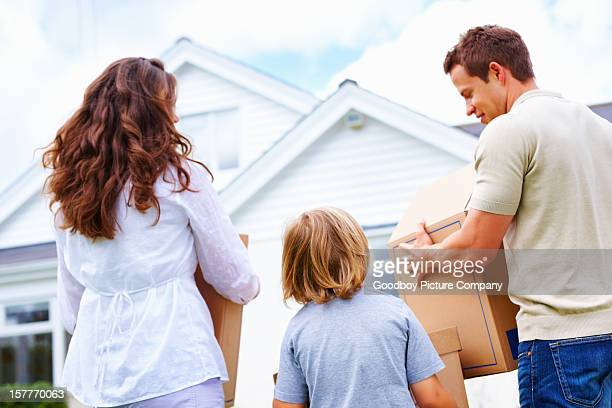 Family with their son holding boxes in front of house
