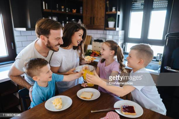 Family with three children having breakfast at home