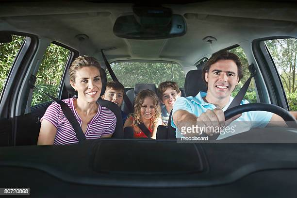 Family with three children (5-11) in car interior portrait