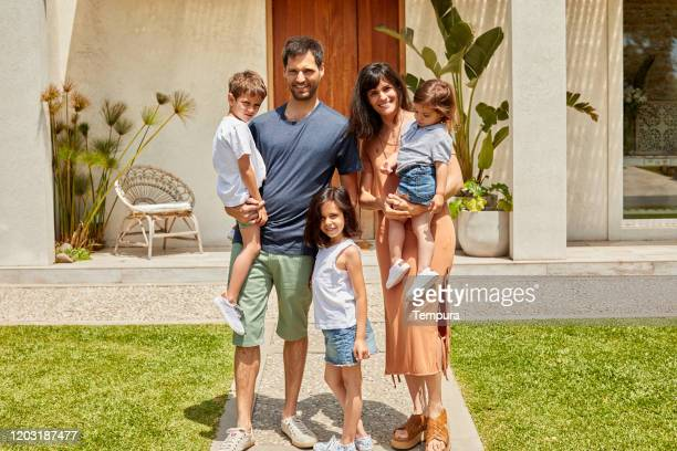 family with three children portrait in front of the house. - five people stock pictures, royalty-free photos & images