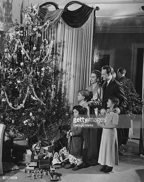 family with three children (4-9) standing at christmas tree, (b&w) - christmas past and christmas present stock pictures, royalty-free photos & images