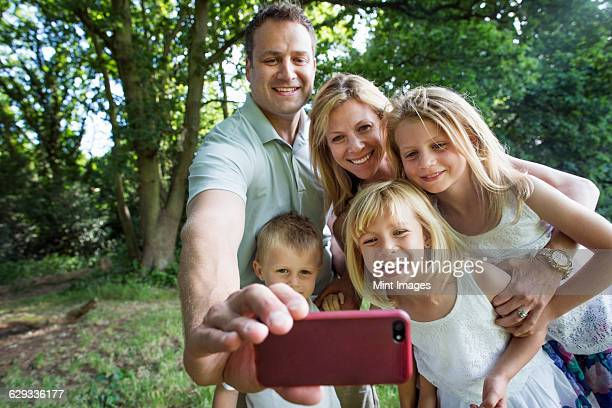 Family with three children, taking a selfie.