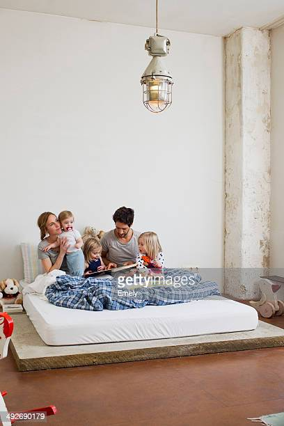 Family with three daughters reading books in bed